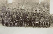 Photograph of group of officers seated in front of wall of Monmouth Castle